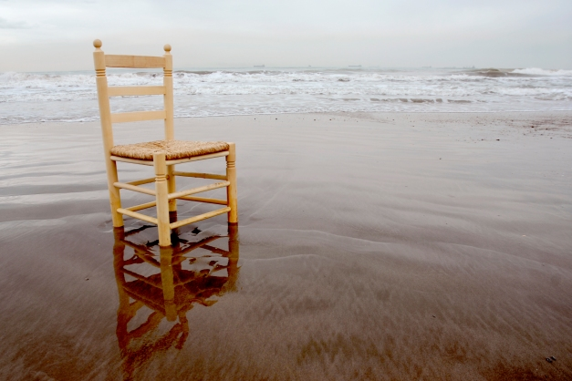 Chair on a beach in the water.